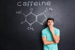 Müder schläfriger Mann, der über Tafel mit gezogenem Koffeinmolekül gähnt Stockfotos