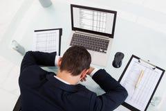 Müder schlafender Geschäftsmann bei der Berechnung von Ausgaben im Büro Stockbild