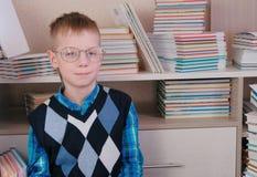 Müder siebenjähriger Junge mit den Gläsern, die auf dem Boden unter den Büchern sitzen Lizenzfreies Stockbild