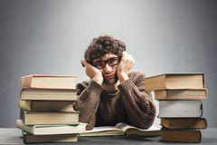 Müder Student, der hinter den Büchern sitzt Stockbild