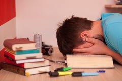Müder Student, der seinen Kopf in seinen Händen mitten in einem Buch stillsteht Lizenzfreie Stockfotos