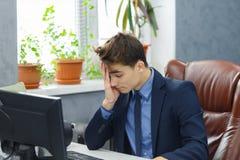 Müder trauriger deprimierter Geschäftsmann im Gesellschaftsanzug, der am Computer im Büro arbeitet Lizenzfreies Stockfoto