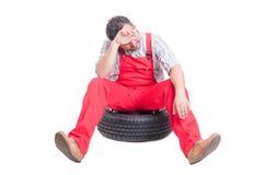 Müder und erschöpfter Mechaniker, der auf einem Autorad sitzt Stockfotografie