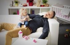 Müder Vater, der mit Baby auf seinem Schoss schläft stockbilder