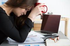 Müder weiblicher Angestellter am Arbeitsplatz im Büro, das Tasse Tee hält Stockbilder