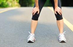 Müder weiblicher Läufer, der eine Pause nachdem dem Laufen macht Stockbild