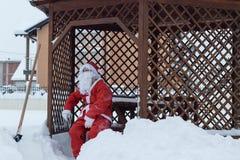 Müder Weihnachtsmann, der nach der Arbeit auf Holzstuhl des Schnees Rem sitzt Stockfotografie