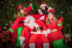 Müder Weihnachtsmann mit Elfenhelfer-Schlafstuhl Stockbilder
