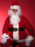 Müder Weihnachtsmann steht still, indem er auf einem Stuhl sitzt Lizenzfreie Stockfotografie