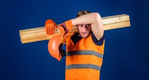 Müdes Arbeiterkonzept Mann beim Abwischen des Sturzhelms und der Schutzhandschuhe geschwitzt von der Stirn, blauer Hintergrund ti Lizenzfreies Stockbild