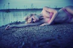 Müdes blondes Mädchen, das auf dem Strand liegt Stockbilder