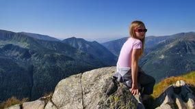 Müdes blondes Mädchen, das in den Bergen sitzt Lizenzfreie Stockfotografie