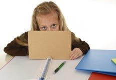 Müdes des kleinen Schulmädchens trauriges und gebohrtes Papier halten mit leerem Kopienraum für das Addieren des Textes Lizenzfreie Stockfotografie