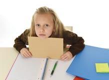 Müdes des kleinen Schulmädchens trauriges und gebohrtes Papier halten mit leerem Kopienraum für das Addieren des Textes Stockbilder