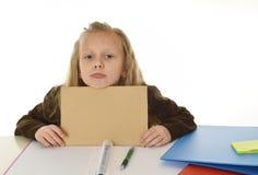 Müdes des kleinen Schulmädchens trauriges und gebohrtes Papier halten mit leerem Kopienraum für das Addieren des Textes Stockfotos