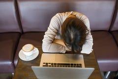 Müdes, erschöpftes Mädchen neben Laptop und Tasse Kaffee stockbilder
