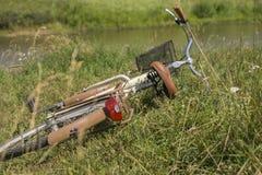 Müdes Fahrrad, das im Gras am Straßenrand liegt Stockbild