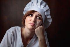 Müdes junges schönes Mädchen in einer Chefuniform lizenzfreie stockfotos
