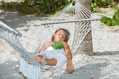 müdes kleines Mädchen, das auf Hängematte im Garten liegt und schläft Lizenzfreie Stockfotografie