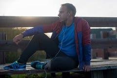 Müdes Läufersitzen, entspannend und hören auf Lizenzfreie Stockbilder