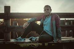 Müdes Läufersitzen, entspannend und hören auf Musiktelefon auf einem hölzernen Pier, Sport Stockfotografie