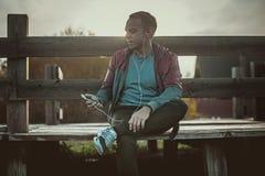 Müdes Läufersitzen, entspannend und hören auf Musiktelefon auf einem hölzernen Pier, Sport Lizenzfreie Stockbilder