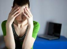 Müdes Mädchen auf dem Hintergrund eines geöffneten Laptops stockfotos