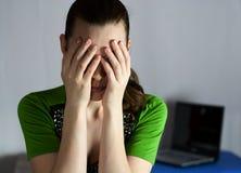 Müdes Mädchen auf dem Hintergrund eines geöffneten Laptops stockbilder