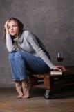 Müdes Mädchen, das mit Glas Wein aufwirft Grauer Hintergrund Stockfotografie