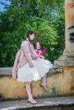 Müdes Mädchen mit einem rosa Gewehrstillstehen stockfoto