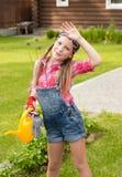 Müdes Mädchen wischt den Schweiß von seiner Braue ab, nachdem sie im Garten gearbeitet hat Stockbilder