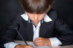 Müdes Schuljungenschreiben im Notizbuch Lizenzfreies Stockfoto