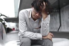 Müdes und gebohrtes asiatisches Geschäftsmannsitzen und -gefühl frustriert lizenzfreie stockfotografie