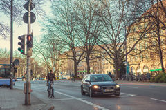 München, Duitsland, 29 December, 2016: Een auto en een fietser bevinden zich bij een verkeerslicht in München Het stadsleven Het  stock afbeelding