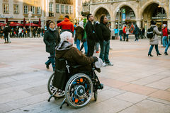 München, Duitsland, 29 December, 2016: Een bejaarde in een rolstoel onderzoekt de gezichten van München op het belangrijkste vier Stock Afbeelding