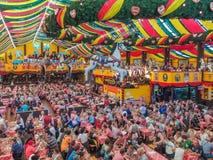 München, Duitsland - 23 September 2013 De Oktoberfestmensen zitten bij grote lijsten in de Hippodrom-tent stock foto