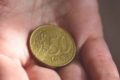 Münze übergibt des Eurocent-50 in der Palme einer Frau A Lizenzfreie Stockbilder