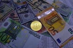 Münze bitcoin liegt auf Banknoten und Blättern mit Zahlen Lizenzfreies Stockbild