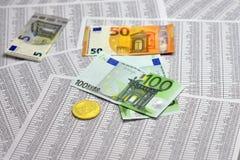 Münze bitcoin liegt auf Banknoten und Blättern mit Zahlen Stockfoto
