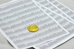 Münze bitcoin liegt auf Blättern mit Zahlen Lizenzfreie Stockfotos