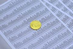 Münze bitcoin liegt auf Blättern mit Zahlen Stockfotografie