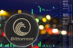 Münze cryptocurrency bittorrent auf Nachtstadthintergrund und -diagramm lizenzfreie stockfotos