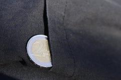 Münze des Euro zwei, die von einer Tasche hervorsteht Lizenzfreie Stockbilder