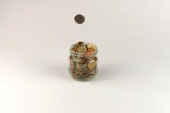Münze fällt in das Glas voll von Münzen stockbild
