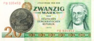 Münze mit 2 Kennzeichen gegen historische Kennzeichenbanknote mit 20 Ostdeutschen stockbilder