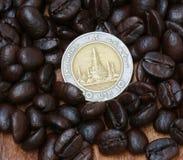 Münze und Kaffeebohnen Stockbilder