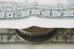 Münze unter Banknote. Stockfoto