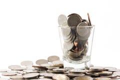 Münzen über dem Glas sind mit Habsucht des Menschen vergleichbar lizenzfreie stockbilder