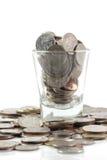 Münzen über dem Glas sind mit Habsucht des Menschen vergleichbar stockbild