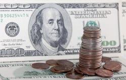 Münzen über hundert Dollarscheinen schließen herauf Ansicht Stockfoto